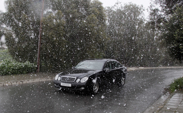 A car passing by the snowin...